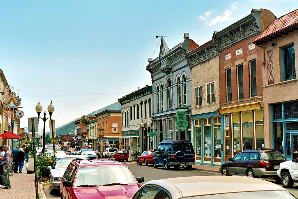 Picture of Miner street in Idaho Springs, lots of colorful cars and buildings with mountains in background