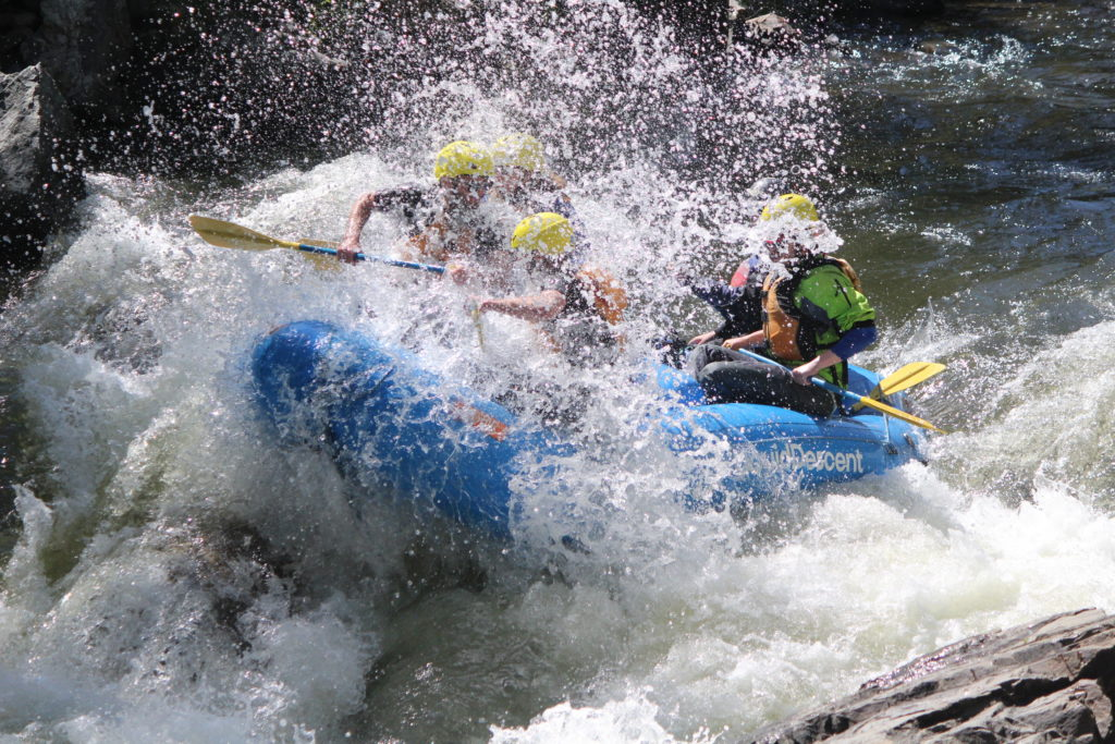 Blue raft hitting wave on Clear Creek and splashing four people wearing helmets and holding paddles