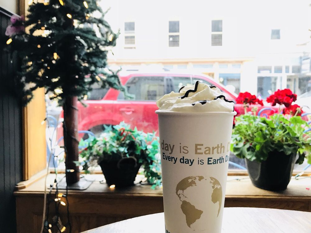 Coffee cup with whipped cream in front of window seat with lots of flowers looking out on street
