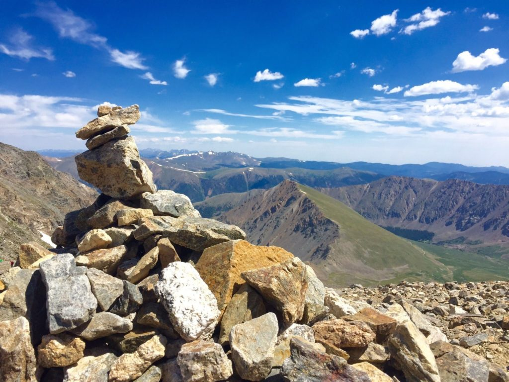 Image of rock pile from top of mountain, lots of mountains in background