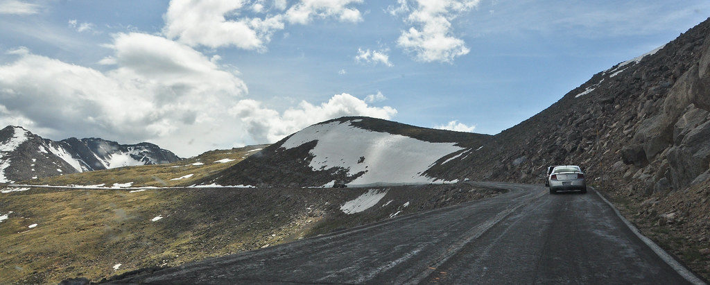 Paved road with two cars on high alpine pass with some snow