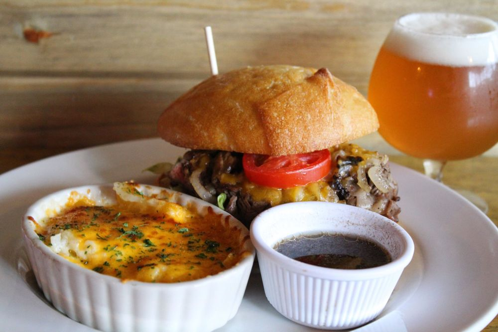 Plate with Hamburger with mushrooms, onions, and cheese and tomato, with a side dish of mac and cheese and au jus with glass of beer on side