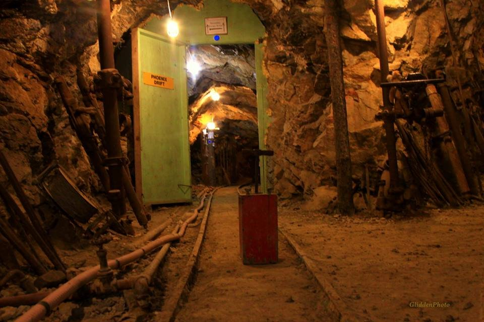 Underground mine with train tracks and green door, open to more rocky tunnel