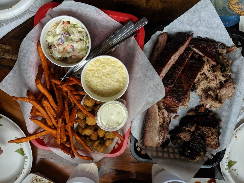 Bird's eye view of two baskets, one basket of four different smoked meats, the other with sweet potato fries, fried okra, mac and cheese and cole slaw